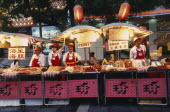 Food stalls in Donghua Yeshi night market with Chinese lanterns hanging above.