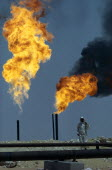 Flaming gas on oil field with man standing behind pipe in foreground.