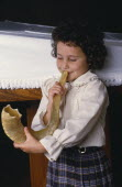 Young Jewish girl blowing the Shofar.