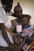 Nurse comforting mother with child with malaria in hospital in Orukinga refugee camp near the Rwandan border.