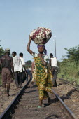 Young woman dressed in traditional local textiles carrying bundle on her head as she walks along railway track to market.African Central Africa Classic Classical Cloth Female Women Girl Lady Historic...