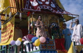 Hare Krishna taking part in a parade on Brighton seafront  with a colourful painted carriageEuropean Colorful Great Britain Northern Europe Religion UK United Kingdom