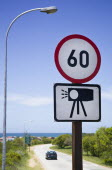 Road sign showing speed limit and warning of radar cameras.