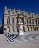 Versailles. Part view of palace with steps and white urn  arched windows and blue sky