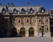 Versailles. Part of palace with statues on walls  arches  balustraded roof and gravel in foreground
