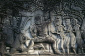 The Bayon.  Detail of bas relief carving on south wall depicting scenes of war.  Khmer soldiers spearing Cham soldiers wearing head dress.Asian Cambodian Kampuchea Southeast Asia History Kamphuchea