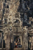 The Bayon.  Tourists framed in doorway of temple complex with relief carving above the lintel.Asian Cambodian Kampuchea Religion Southeast Asia History Holidaymakers Kamphuchea Religious Tourism