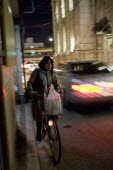 Gion District.  Japanese woman riding her bicycle at night along a side road in Kyoto carrying bag of shopping in basket on the handlebars with car passing in the opposite direction.vehicletransport...