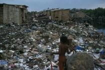 The city rubbish tip in barrio Guayas slum neigbourhood with children playing near large rock in the foreground.American Equador Hispanic Kids Latin America Latino Neighbourhood District shanty South...