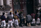 Quiche Indian men kneeling in prayer outside the 16th century church during San Andres Festival on December 8thPrayingAmerican Central America Hispanic Latin America Latino Male Man Guy Religious