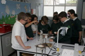 Food technology science pupils carrying out an experiment to measure the evaporation of a salt solution using a bunsen burner.European Immature Kids Learning Lessons Teaching