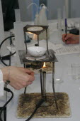 Teacher lighting a bunsen burner prior to it being used for a food technology experiment measuring the evaporation of a salt solution.European Immature Kids Learning Lessons Teaching