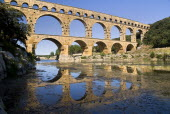 Pont du Gard.  View from west side of the Roman aqueduct in glowing evening light with reflection in the water below.Bridge arch European French Western Europe Warm Light