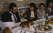 Jewish New Year.  The chala or bread is passed along table during festival meal in family home. European Great Britain Kids Northern Europe Religion Religious Judaism Jew Jews UK United Kingdom