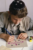 Boy at Sunday school wearing a kippah and making a card with Hebrew lettering.European Great Britain Kids Learning Lessons Northern Europe One individual Solo Lone Solitary Religion Religious Judaism...