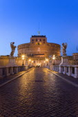Castel Sant Angelo illuminated at night with tourists on the Ponte Sant Angelo bridge over the River Tiber lined with statues of winged angelsEuropean Italia Italian Roma Southern Europe History Holi...