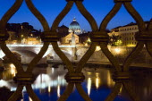 The Dome of the Basilica of St Peter in the Vatican City illuminated at night with the Ponte Vittorio Emmanuel II bridge across the River Tiber in the foreground all seen through iron railings on the...