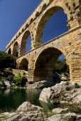 Pont du Gard.  Angled view of three tiers of arches from the west side in glowing evening light.  Large rocks extending from bank in the foreground.Bridge arch Roman aqueduct European French Western...