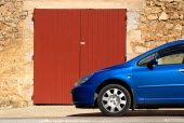 Roussillon.  Blue car parked outside red painted doorway set into exterior wall of one of the red stone buildings of the town.European French Western Europe 1 Automobile Automotive Cars Motorcar Sing...