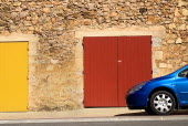 Roussillon.  Blue car parked outside red stone building with red and yellow painted double doorways.European French Western Europe 1 Automobile Automotive Cars Motorcar Single unitary Automobiles Aut...