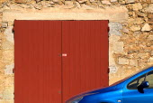 Roussillon.  Part view of blue car parked outside town building of red stone with red painted double doorway.European French Western Europe 1 Automobile Automotive Cars Motorcar Single unitary Automo...