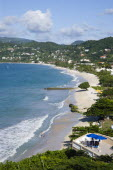 Waves breaking on the long stretch of Grand Anse Beach with people in the surf and on the beach with the inland hills in the distanceScenic West Indies Beaches Caribbean Grenadian Greneda Holidaymake...