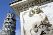 Campo dei Miracoli or Field of Miracles Carving of a cherub and bearded male face on a water fountain in front of the Leaning Tower belltower or Torre Pendente under a blue skyEuropean Italia Italian...