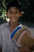 Portrait of boy holding school books.Asia Asian Bangladeshi Kids Learning Lessons One individual Solo Lone Solitary Teaching Asia Asian Bangladeshi Kids Learning Lessons One individual Solo Lone Sol...