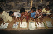 Schoolboys sitting on mats on floor of village school learning to read African Asia Asian Bangladeshi Kids Lessons Teaching African Asia Asian Bangladeshi Kids Lessons Teaching