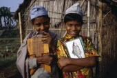 Three-quarter portrait of two  smiling young boys carrying books and writing board standing outside thatched hut.2 Asia Asian Bangladeshi Happy Immature Kids Contented Learning Lessons Teaching Young...
