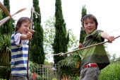 Twin boys playing with bow and arrows made from tree branches and stringUKEnglandFamilyBrothersTwinTwinsPlayingPlayGamesFunMal British Isles European Great Britain Immature Kids Northern Eu...