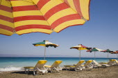 Ixia beach resort popular for water sports with part seen red and yellow striped sun umbrella in foreground against blue  cloudless sky.  Line of sun loungers and parasols overlooking sea beyond.Aege...