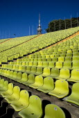 Germany, Bavaria, Munich, Olympic Stadium, The colourful green seats in the stadium with the Olympic Tower behind.