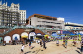 England, East Sussex, Brighton, Young people playing beach volleyball on sand on the seafront with the De Vere Grand Hotel and The Brighton Centre beyond.