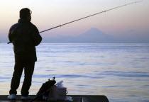 Japan, Honshu, Chiba, Tateyama, man fishing in Tokyo Bay, Mount Fuji visible across the water.