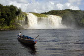 VENEZUELA, Bolivar State, Canaima National Park, Canaima Village, A Pemon tribe man while sailing with his boat at Canaima lake just in front of a big waterfall on a bright day with blue sky and white...
