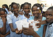 HAITI, Isla de la Laganave, School children holding plastic cups of water from plumbing paid for by Lemon Aid Scottish Charity.