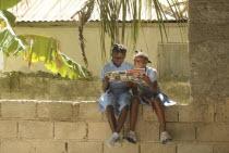 HAITI, Isla de la Laganave, young school girls sat on wall reading geography magazine.