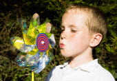 Children, Toys, Outdoors, Young boy blowing toy windmill gently.