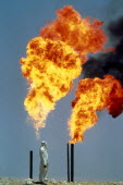 Saudi Arabia, Arab man standing next to gas burning off from oil well.