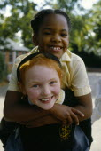 England, West Midlands, Birmingham, Smiling young girls in school playground with the white girl giving her black friend a piggy back.