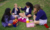 England, East Sussex, Brighton, Four young schoolgirls sitting on the grass in the school playing fields having their home packed lunch meals from their lunchboxes.