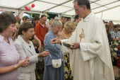 Religion, Christian, Catholic, Worshippers receiving holy communion in their hands from priest.