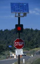 Environment, Solar Power, USA, California.  Solar powered red warning light on traffic light next to road side.