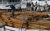Indonesia, Java, Jakarta, Group of men unloading timber from ship in dockyard.