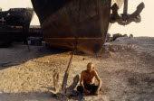Uzbekistan, Near Aral Sea, Indigenous old man sitting beside a beached boat and anchor