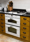 Architecture, Interiors, Kitchen, White domestic gas hob and electric oven household appliance set under worktop in fitted integrated kitchen.