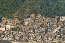 BRAZIL Rio de Janeiro Favela or slum on hillside above Copacabana neighbourhood, steep road through slum rock face and tree cover antenna in foreground.