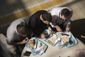 Hungary, Pest County, Budapest, looking down on three young men seated at circular table having lunchtime meal of Hungarian sausages, bread and pickles at the Central Market Nagy Vasarcsarnok. Mobile...