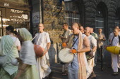 Hungary, Pest County, Budapest, Hare Krishna devotees singing and dancing on Andrassy UtIn Pest, with graffiti covered doorway behind. The International Society for Krishna Consciousness or ISKCON, al...